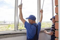 Craftsmen workers install window in house rattle with a special rubber hammer stock photos