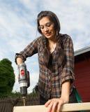 Craftsperson-Frau benutzt hölzernen die Energie-Schraubenzieher-Bohrlöcher Stockfotografie