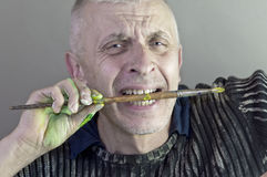 Craftsperson With Paint Brush. An emotional portrait of a male craftsperson holding a paint brush with his teeth. Studio portrait, concept of creativity royalty free stock photography