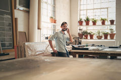 Craftsperson talking on phone in workshop studio. Handsome craftsman standing casually in his workshop studio talking on his phone with a positive expression stock image