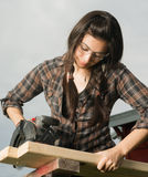 Craftsperson Woman Uses Circular Saw Cutting Wood. Brunette woman in pigtails cuts 2x4 boards with battery operated saw stock image
