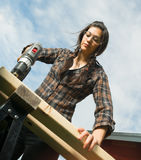 Craftsperson Woman Uses Power Screwdriver Drilling Holes Wood. Brunette woman in pigtails drilling 2x4 boards with battery operated drill stock photo