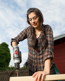 Craftsperson Woman Uses Power Screwdriver Drilling Holes Wood. Brunette woman in pigtails drilling 2x4 boards with battery operated drill stock photography