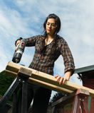 Craftsperson Woman Uses Power Screwdriver Drilling Holes Wood. Brunette woman in pigtails drilling 2x4 boards with battery operated drill royalty free stock photo