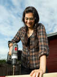 Craftsperson Woman Uses Power Screwdriver Drilling Wood Project. Brunette woman in pigtails drilling 2x4 boards with battery operated drill stock image