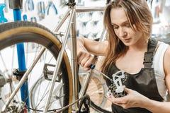 Craftswoman agradável diligente que renova o pedal na garagem Imagem de Stock