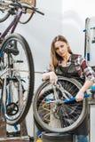 Craftswoman concentrato che ripara la ruota nel garage Fotografia Stock Libera da Diritti