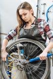 Craftswoman conscio che ripara la ruota nell'officina Fotografie Stock