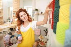 Craftswoman dai capelli rossi che solleva la sua mano per la presa del filo Fotografie Stock Libere da Diritti