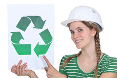 Craftswoman displaying recycling sign. Happy female manual worker displaying a recycling sign Royalty Free Stock Image
