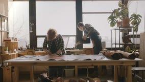 In craftswoman esperto professionista che prepara tagliare un grande pezzo di cuoio su una tavola in un'officina fabbricante mode video d archivio