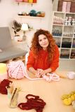 Craftswoman with foxy hair working with crochet hook. Crochet hook. Professional young craftswoman with nice foxy hair feeling overloaded while working with Stock Images