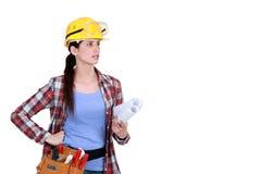 Craftswoman holding blueprints Royalty Free Stock Photo