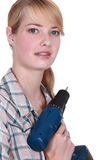 Craftswoman holding a drill Royalty Free Stock Images