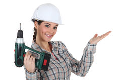 Craftswoman holding a drill Royalty Free Stock Image