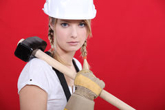 Craftswoman holding a huge hammer Royalty Free Stock Photos