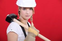 Craftswoman holding a huge hammer. A craftswoman holding a huge hammer Royalty Free Stock Photos