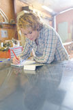 Craftswoman holding notepad and writing Royalty Free Stock Photography