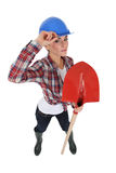 Craftswoman holding a shovel. And making a helmet tip Royalty Free Stock Photography