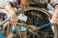 Craftswoman laborioso che ripara la catena della bicicletta Immagini Stock