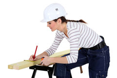 Craftswoman measuring a board Royalty Free Stock Photo