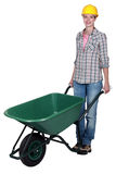 Craftswoman pushing a wheelbarrow Stock Photography