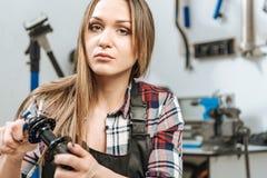 Craftswoman sicuro che ripara il dettaglio nell'officina riparazioni fotografia stock