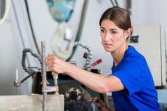 Craftswoman in stonemason workshop. Female stonemason adjusting workpiece in polishing machine Stock Photos