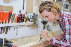 Craftswoman working with chisel and hammer in workshop Stock Images