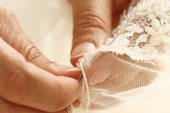 Craftwoman sews. A fine fabric royalty free stock photos