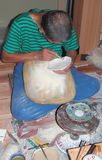 Craftworker. A man working to decorate some ceramic craft-works royalty free stock photo