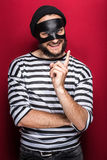 Crafty bandit smiling and threaten with finger. On red background Stock Images