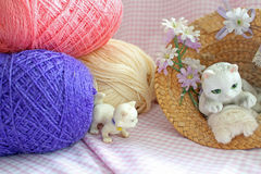 Crafty Cats. This photo shows an ornament cat resting on a ball of wool and sitting in a straw hat while the kitten is playing mischievously near by and on a Royalty Free Stock Image