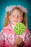 Crafty girl with big lollipop. Over blue background Stock Photography