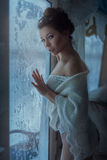 Crafty girl look. Beautiful girl sly looks standing near the winter window Stock Photos