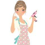 Crafty glue gun woman. Woman with pink glue gun and floral apron Stock Photo