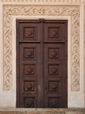 Crafty wooden door. On decorated stucco wall Stock Images