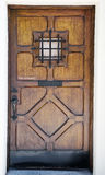 Crafty wooden door with small window. And metal railing on stucco wall Royalty Free Stock Photo