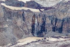 Craggy cliff face with snow and ice melting into waterfall. In summer at mount rainier royalty free stock images