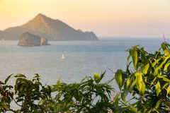 Craggy peaks and rocky coastline of southern thailand in the Ind. Ian ocean on a warm breezy night the sun crests the horizon. Sailors delight stock photo