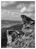 Craggy rocks with horizon. Craggy rocks foreground against a black and white landscape of hills royalty free stock photos