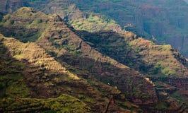 Craggy rocks in Waimea Canyon. Waimea Canyon on Kauai with side lit ridges on the mountainside stock image