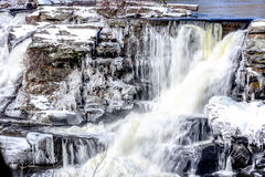 Craggy waterfall. Waterfall on a freezing cold day with ice hanging from craggy rocks stock photo