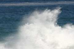 Crahing wave. Wave crashing againt rocks with white plumes of spray Royalty Free Stock Photo