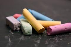 Craie d'école de couleur sur un noir Photo stock