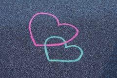 Craie de dessin de deux coeurs sur l'asphalte Photos libres de droits