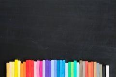 Craies colorées alignées sur la bannière de fond de tableau noir Images libres de droits