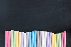 Craies colorées alignées sur le fond de tableau noir Photos stock