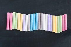 Craies colorées alignées sur le fond de tableau noir Image libre de droits