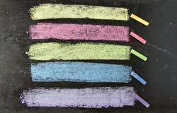 Craies colorées sur le fond de tableau noir Image stock